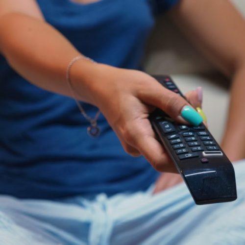 Switching tv programs sitting on sofa